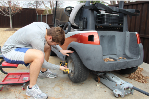 Coppell High School senior Thomas Donaldson works on one of his golf carts in his backyard for Tom Carts, a self run business he began on his own. Donaldson refurbishes the golf carts and sells them for profit. Photo by Meara Isenberg.