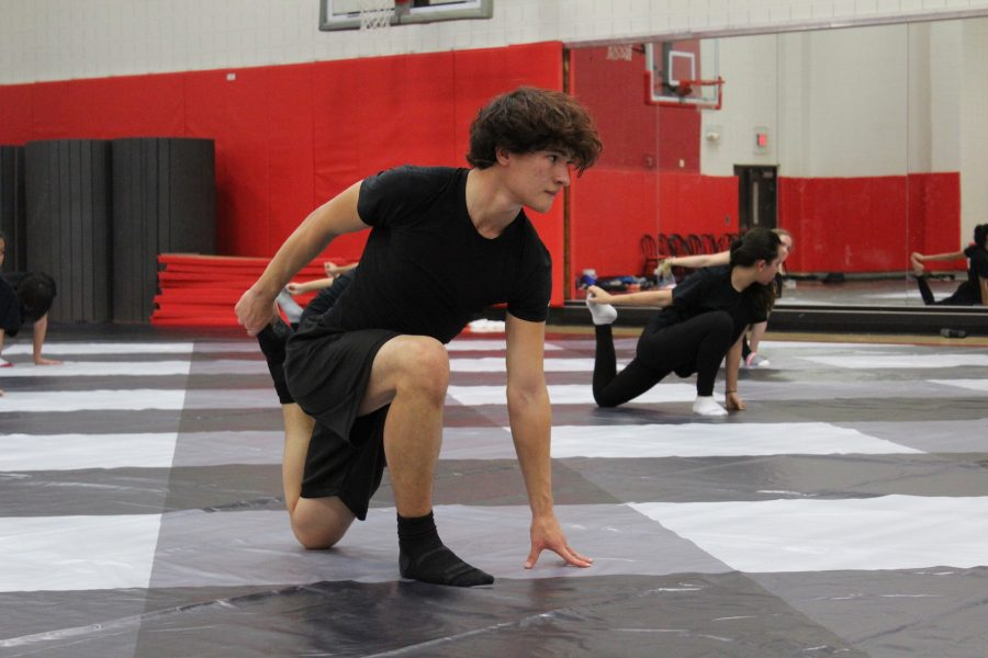 Coppell High School senior Brandon Medel stretches his quads before beginning to dance in the small gym Wednesday night at the JV practice. Brandon is one of two boys in the JV Winter Guard, and one out of the three total in the Coppell Color Guard.