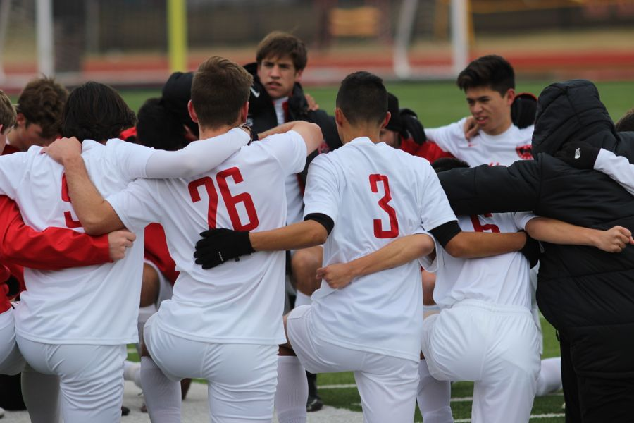 The Cowboys soccer team kneels to pray before the game at Buddy Echols Field on Jan. 5. The Cowboys defeated Lewisville, 2-1, to start the season with a win.