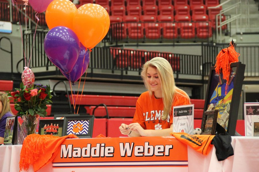 Coppell+High+School+senior+Maddie+Weber+cheers+on+another+signee+as+they+sign+their+letter+of+intent+a+on+Monday+morning.+Weber+signed+on+with+Clemson+University+to+continue+her+soccer+career.+In+the+CHS+arena%2C+12+CHS+seniors+welcomed+their+friends+and+family+to+join+them+for+National+Signing+Day.