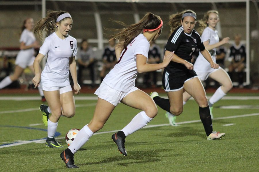 Coppell High School junior midfielder Nicole Henry looks to pass the ball to forward Micayla Weathers during the first half of Tuesday night's game against Lake Highlands. The Coppell Cowgirls claimed a 3-0 victory over the Lake Highlands Lady Wildcats. Photo by Amanda Hair.