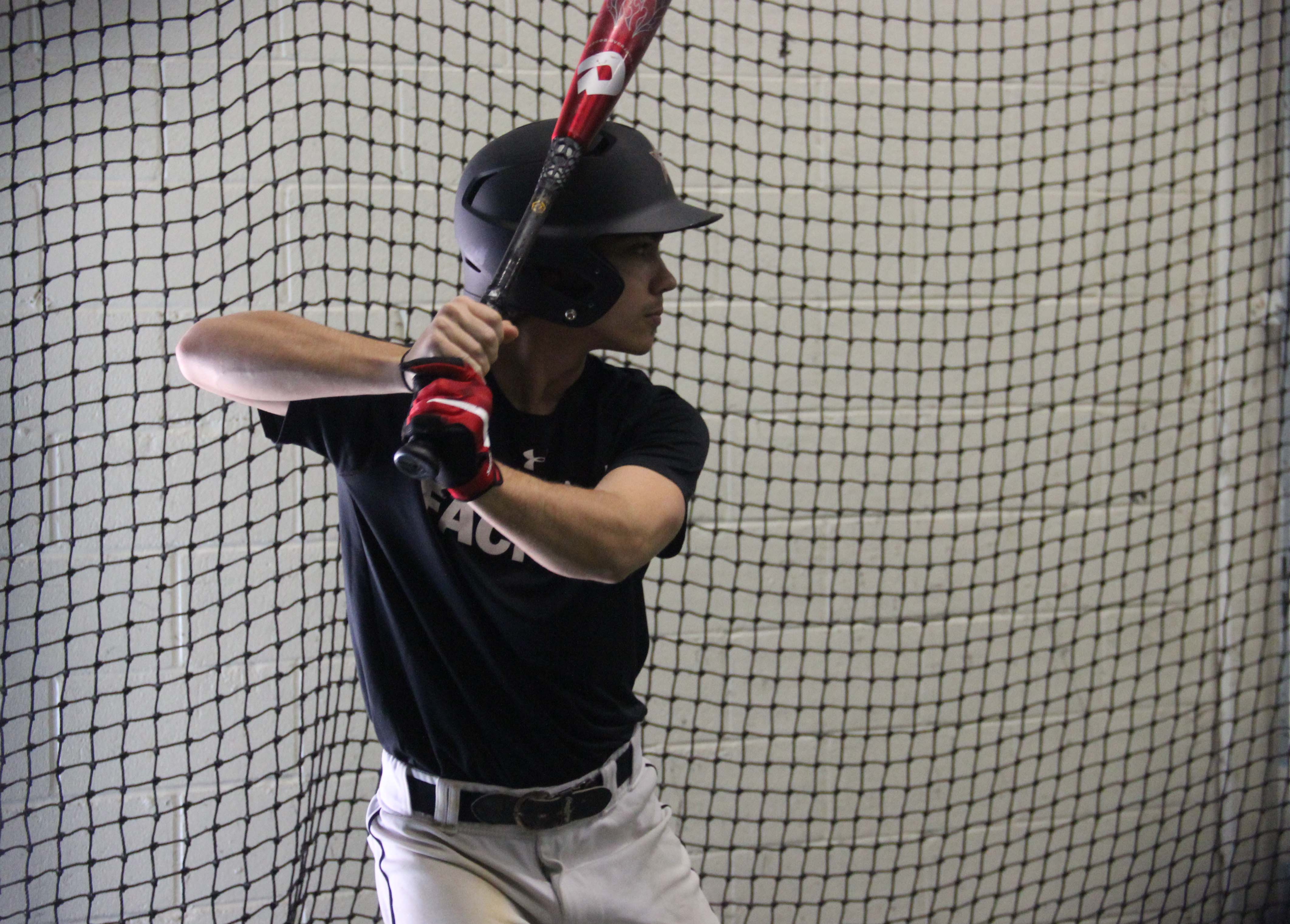 Coppell High School senior Tyler Lozes awaits a pitch in the batting cage at the CHS batting cages on Feb. 21 during fourth period. Lozes, an outfielder, for the Cowboys, is on the Varsity Boy's baseball team.