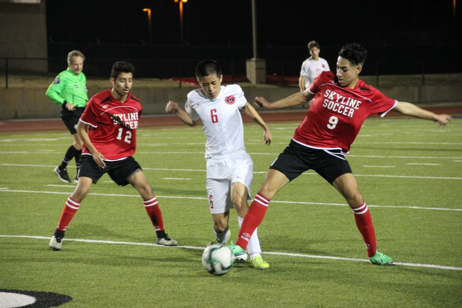Coppell High School junior middlefield and forward Bryon Peng kicks the ball from Skyline player and tries to pass it to Coppell High School junior defender Jacob Turman at the Buddy Echols Field on Friday night. The Coppell varsity boys soccer team won the game 5-1.