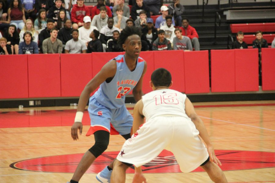 Skyline senior guard Marcus Garrett sizes up Coppell sophomore guard Tariq Aman in the Raiders' 64-45 victory over the Cowboys on Friday night at the CHS arena. Garrett scored 21 in the victory.