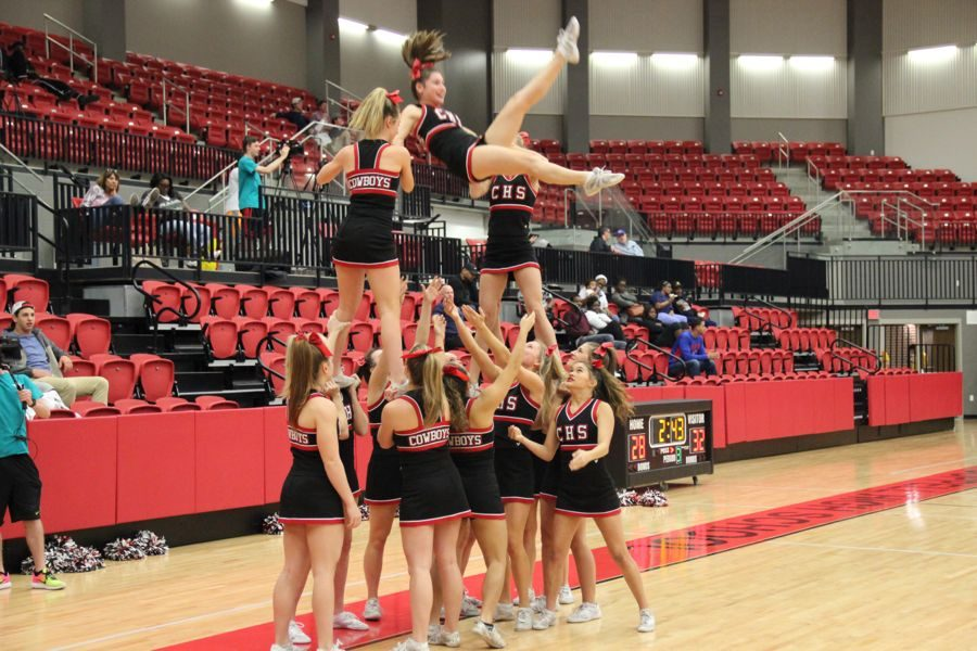 Coppell Varsity cheer performs a stunt during half-time of the basketball game in the CHS arena. Coppell lost 44-39 to the Berkner Rams on Tuesday evening.