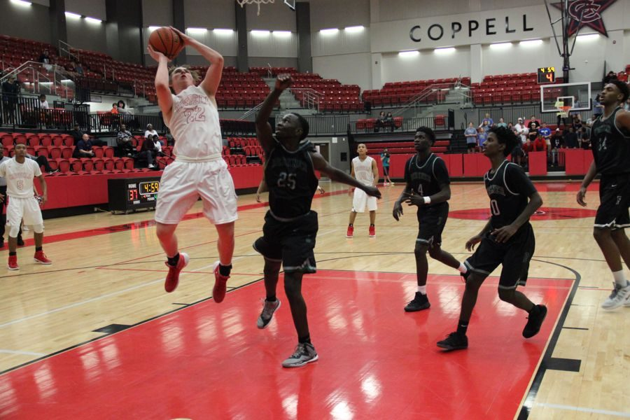 Coppell High School senior Jackson Solari shoots the ball on offense during the last quarter of the game on Tuesday night. The Cowboys lost to the Rams with a close score of 44-39.