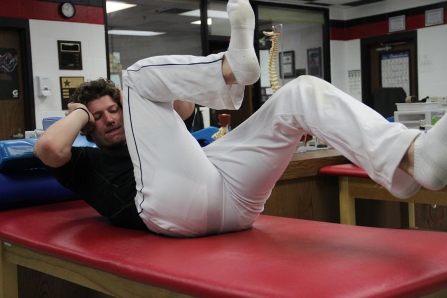 Coppell High School senior varsity baseball player Jacob Nesbit stretches in the CHS training room on Feb. 2 after practice during fourth period. Nesbit attends physical therapy every day after practice in order to strengthen the muscles around the vertebrae that was fractured last fall.