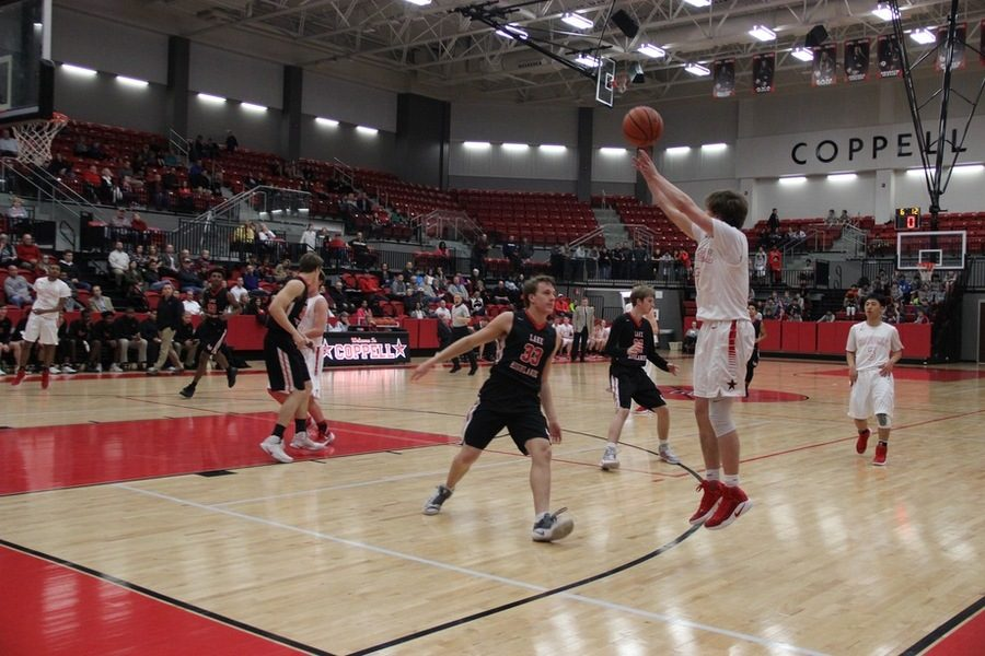 Coppell High School senior Jackson Solari goes up for a shot as senior forward Kameron Hartman defends. Coppell ended Tuesday night's game with a 60-46 victory over Lake Highlands in the CHS arena.