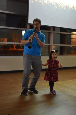Coppell resident Nicolas Garcia plays a jazz song on the clarinet while his daughter dances yesterday night at the Coppell Library. The Library will be hosting open mic nights  the second Wednesday of every month.