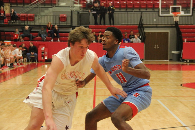 Coppell High School senior forward Sam Marshall pushes past a Skyline player during Friday night's game in the CHS arena. With the score ending at 64-45, the Skyline Raiders went home with a victory over Coppell. Photo by Hannah Tucker.