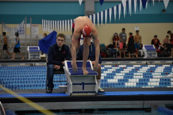 Coppell senior Jonathan Henley prepares to jump off of his platform for the 100 freestyle heat on Saturday morning in the Lewisville ISD Westside Aquatic Center. The swimming team placed fourth overall at the regional meet.