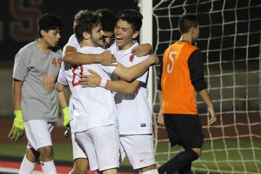 Coppell High School senior forward Jacob Capdevila, junior forward Francisco Redondo, and senior forward Nick Taylor celebrate after Taylor scored the fourth and final goal for the Coppell Cowboys during the second half of Tuesday night's game. The Coppell Cowboys ended the night with a 4-1 victory over the W.T. White Longhorns at Buddy Echols Field.