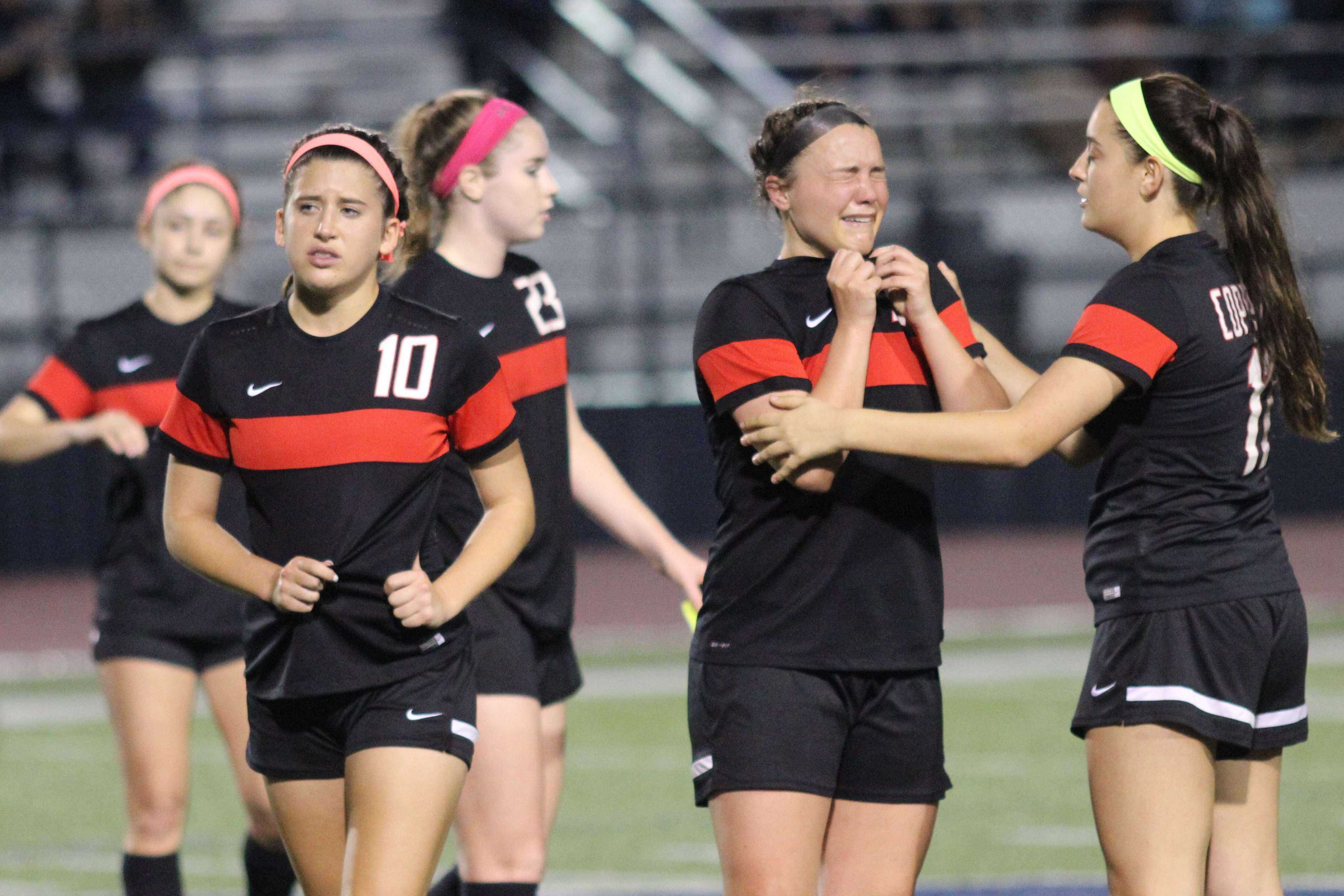 Coppell High School freshman defender Haley Roberson, senior forward Tori Teffeteller, senior defender Sarah Houchin and sophomore midfielder Mary Ziperman all accept defeat after their 1-0 loss to the Sachse Lady Mustangs at Ron Poe Stadium. After a weather delay that lasted over an hour, the Cowgirls could not pull out a victory in the Class 6A Region II quarterfinals.