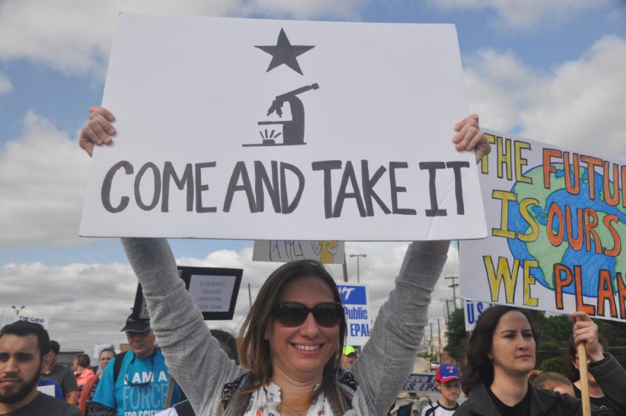 A woman holds up a sign at the March for Science in Dallas on Saturday.  People carried original signs, flags and globes at the march. Photo by Amelia Vanyo.