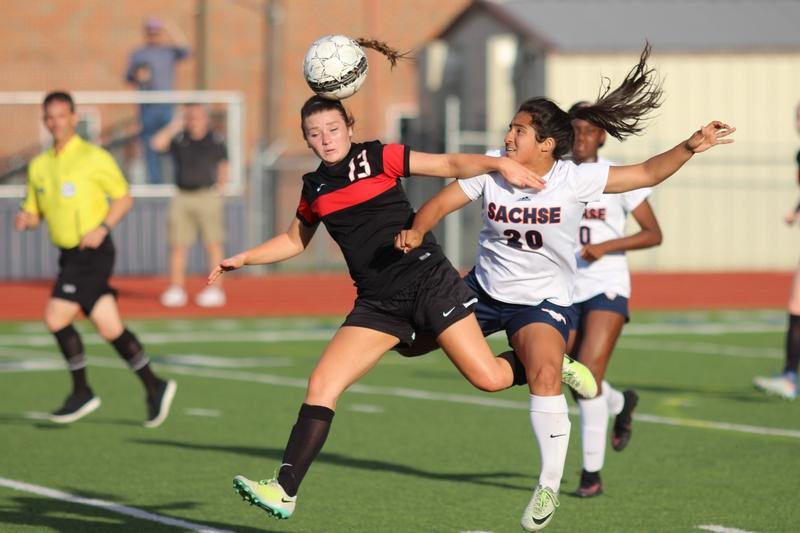 Coppell High School junior Shelby Sylvester jumps to the ball during the first half of Tuesday night's game against Sachse. The Coppell Cowgirls fell to the Sachse Lady Mustangs with a final score of 1-0 at Ron Poe Stadium.