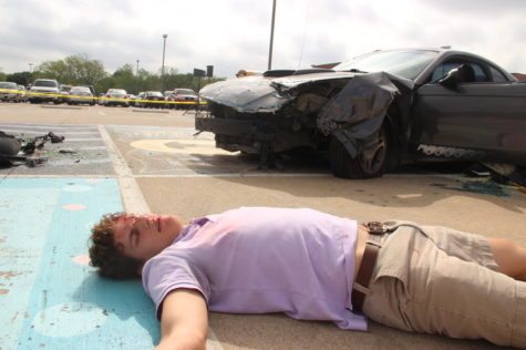 Coppell High School senior Eric Loop lays injured on the ground after being thrown from a car during a drunk driving accident simulation in the CHS parking lot last Thursday for the Shattered Dreams presentation. Loop was thrown from the car during Coppell's biannual Shattered Dreams, a presentation put on by KCBY which reproduces the possible outcomes of a DWI crash in hopes to prevent teenage drinking and driving. Photo by Hannah Tucker.