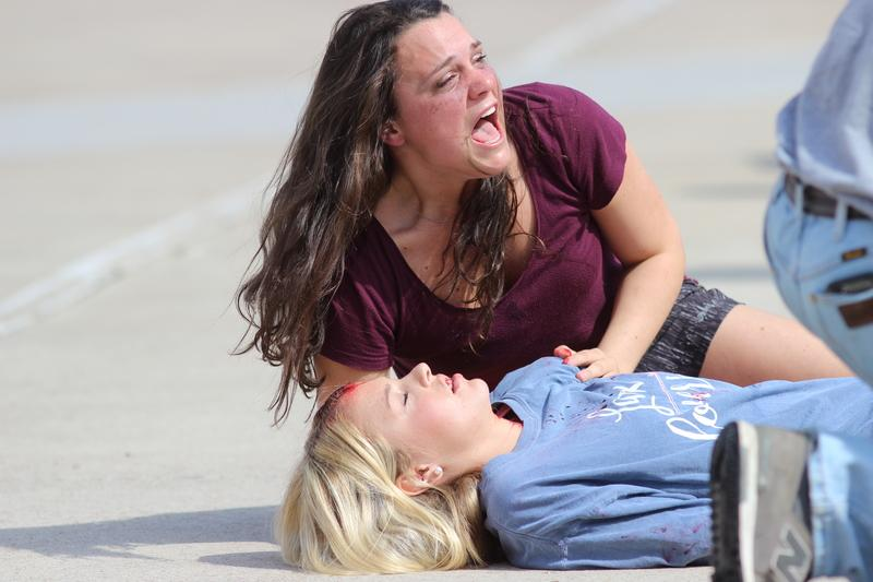 Coppell High School senior Tori Teffeteller screams over CHS senior MaryKathryn Ferguson, who was injured in Shattered Dreams in the CHS parking lot. Shattered Dreams is intended to show juniors and seniors the seriousness repercussions drinking and driving can have on everyone.
