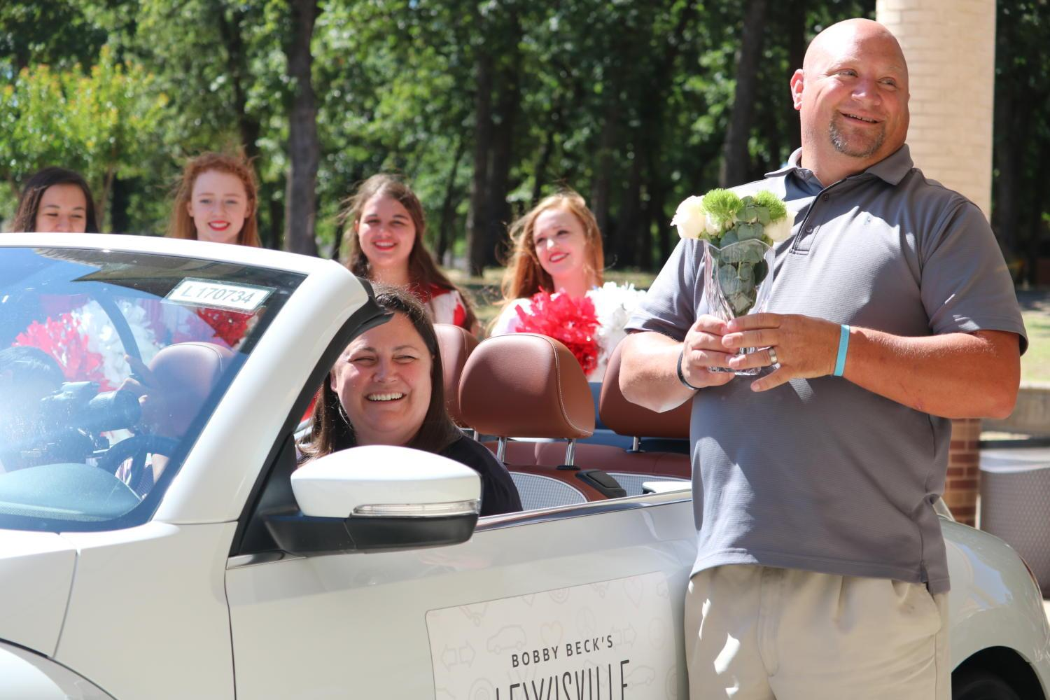 Secondary Teacher of the Year Holly Anderson sits in her new Volkswagen Beetle, with husband Jason Anderson, in front of the school on Thursday during third period. Anderson was surprised by students and administration for her accomplishment.