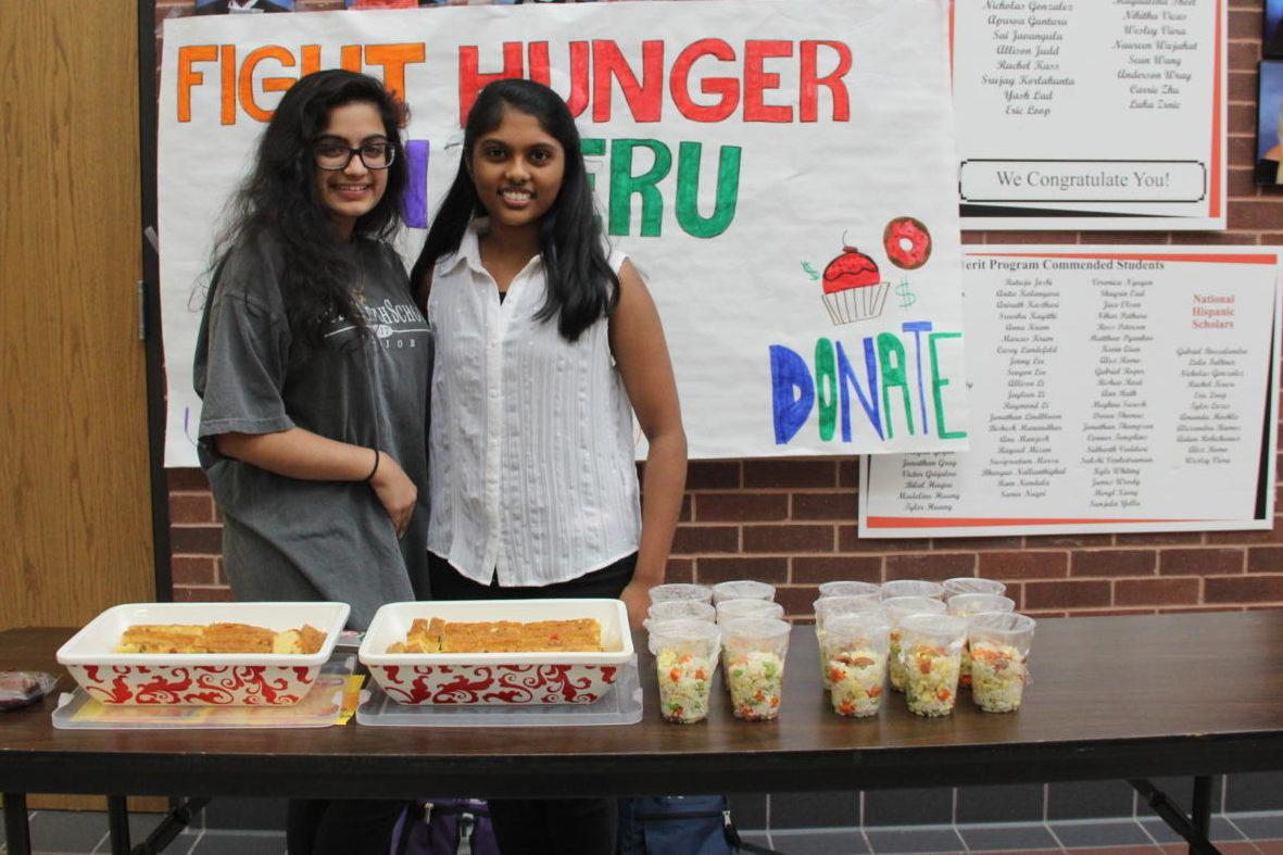 Coppell High School senior Kirtana Kalavagunta (left) and junior Priya Mekala (right) take part in raising money for the hungry in Peru for Darryl Lee's AP Spanish IV classes on Tuesday. The multicultural snack bar includes brownies, fried rice and fruitcake.