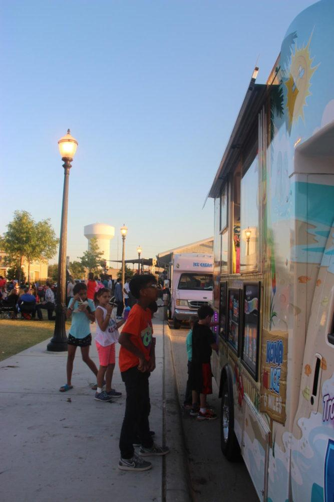Food trucks line up along the sidewalk so that many visitors could purchase food and drinks at the Concert on the Lawn at the Square in Old Town Coppell last night. There were many vendors such as Kona Ice, Dodie's and Frost Cupcakery.