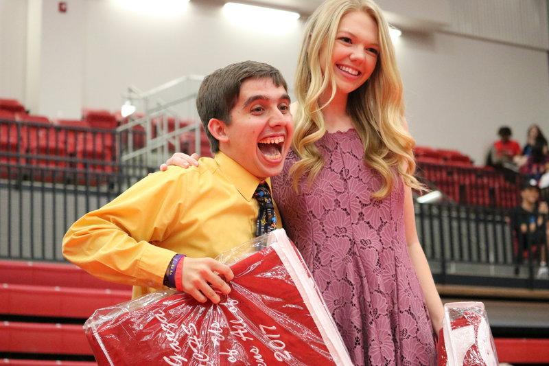 "Coppell High School seniors Marcus Garza and Erin Dempsey step up to the stage to get their award in the CHS Arena on Wednesday morning at Senior Awards. They were given an award for most embodying this year's CHS motto, ""I am CHS."""