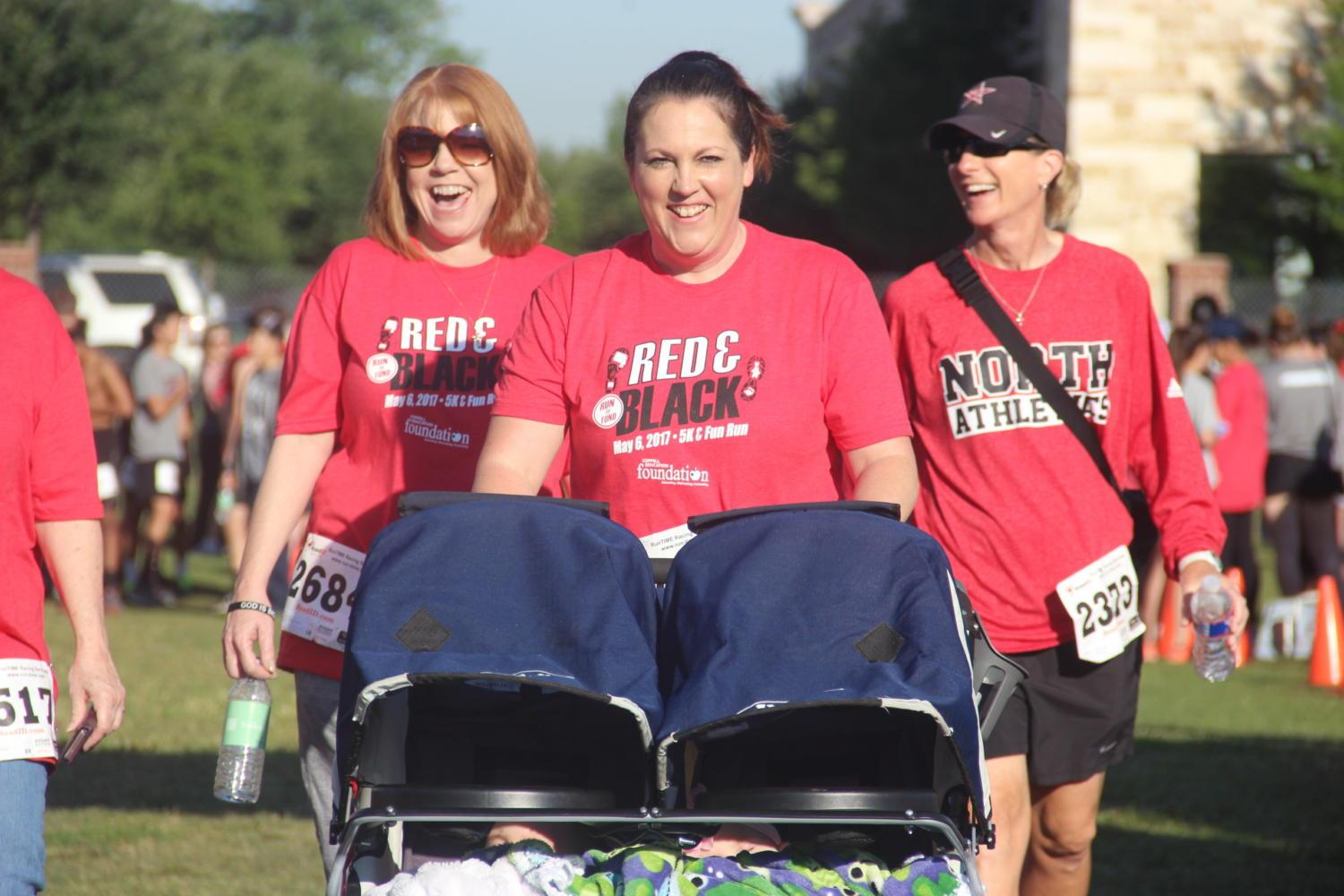 Coppell+Middle+School+North+Principal+Amanda+Ziaer+and+other+women+walk+across+the+finish+line+of+the+one+mile+fun+run.+The+Red+and+Black+Run+to+Fund+took+place+on+Saturday+at+Coppell+Middle+School+North%2C+bringing+people+from+all+different+communities+together.+