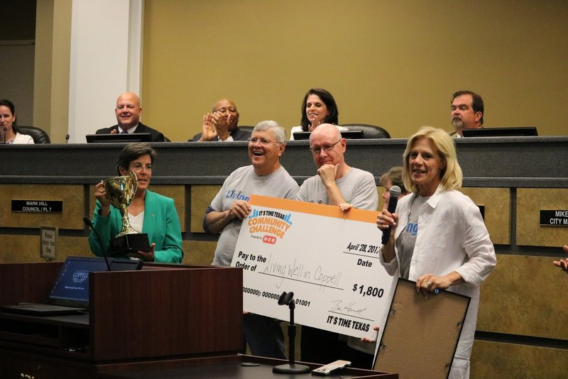 Co-chairs of Living Well in Coppell Sally McCurdy and Ed Guignon come forward to recognize Coppell receiving first place in the ITS TIME Texas Community Challenge for the third year in a row. Living Well in Coppell received a check for $1,800 and showed it at the City Council Meeting on Tuesday night.