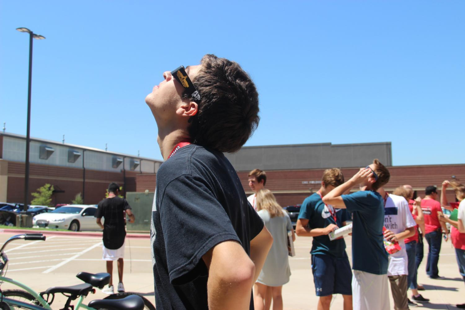 Coppell+High+School+senior+Jordan+Whiteley+observes+the+peak+of+the+solar+eclipse+in+front+of+the+fieldhouse+on+Monday.+All+of+the+students+used+specialized+glasses+or+homemade+viewing+devices+to+safely+experience+the+phenomenon.