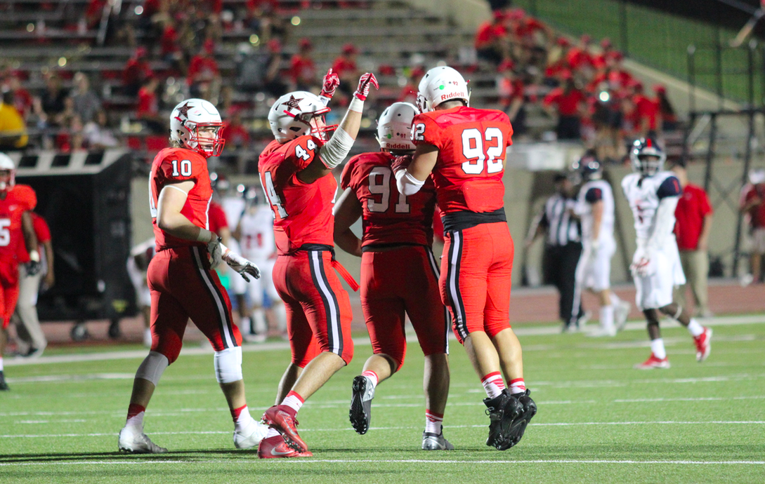 Coppell+High+School+junior+Joseph+Sheddy+congratulates+senior+KK+Moe+for+making+a+good+tackle%2C+as+senior+Pierce+McFarlane+celebrates+with+the+crowd.+The+Coppell+Cowboys+played+against+McKinney+Boyd+at+Buddy+Echols+Field+last+night+and+came+out+with+a+win%2C+34-24.