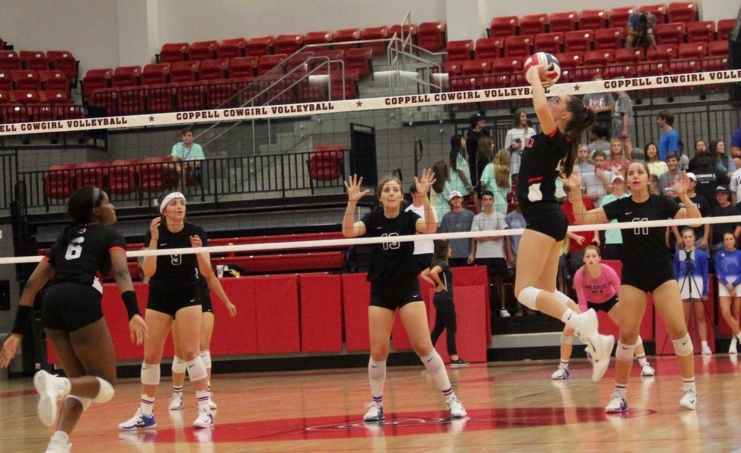 Coppell High School senior defensive specialist Ava Racz sets to junior Amarachi Osuji at the Coppell High School Arena against Pearce on Tuesday night. The Cowgirls defeated the Lady Mustangs, 25-21, 25-23, 24-26, 25-14, in their first home district game.