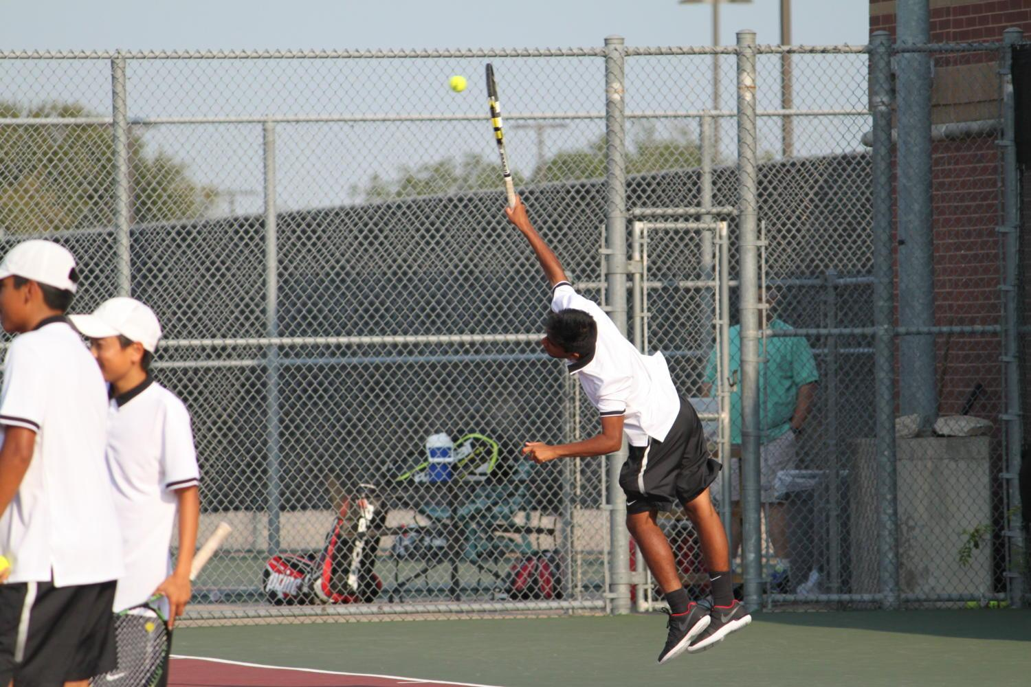Coppell High School senior Yash Reddy jumps up at an opportunity to return a strong shot against Lake Highlands in his doubles match. Reddy and his doubles partner took away a 6-2, 6-1 victory on Sept. 5 at the CHS Tennis Center.
