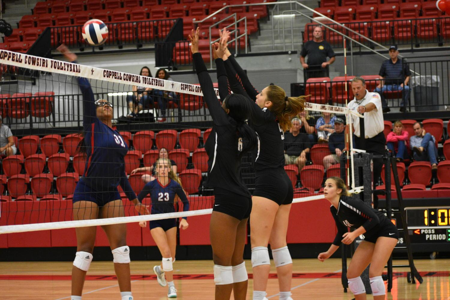 Coppell High School junior Amarachi Osuji and freshman Madison Gilliland jump to make a block during Friday night's game in the Arena. The Cowgirls played against the Allen Eagles and ended the match losing straight sets (27-29, 12-25, 20-25) against the Lady Eagles.