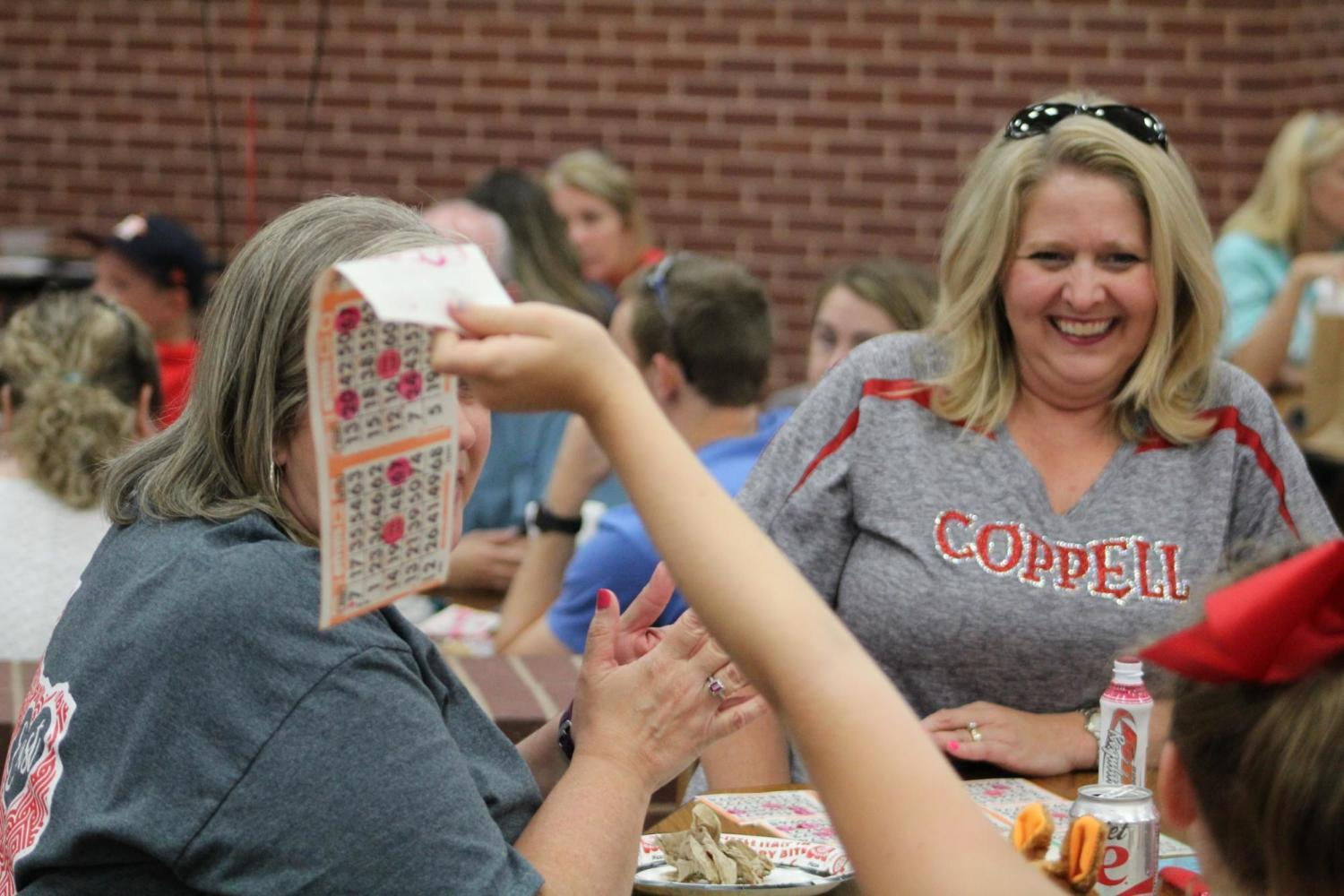 Cheer Bingo's round three winner Lisa Pehl celebrates winning the round with her friends and family on Friday night at Coppell High School during the cheerleaders annual bingo fundraiser. The event has been held for more than 20 years and helps raise funds for the cheerleading program.