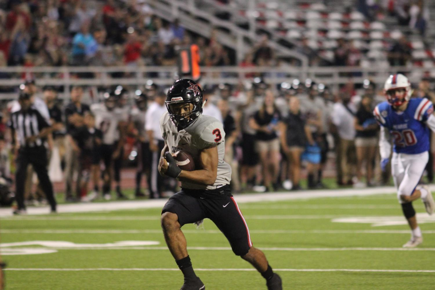Coppell junior safety Jonathan McGill runs the ball through the JJ Pearce defense to later score a touchdown. The Coppell Cowboys played against JJ Pearce Mustangs at the Eagle-Mustangs Stadium in Richardson with the Cowboys winning the score of 28-21.