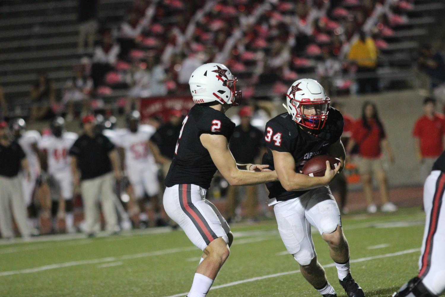 Coppell Cowboys senior quarterback Brady McBride passes the ball to junior running back Ryan Hirt during the fourth quarter of the Homecoming game on Oct. 13 at Buddy Echols Field. The Coppell Cowboys defeated the Lake Highlands Wildcats with a final score of 49-34.