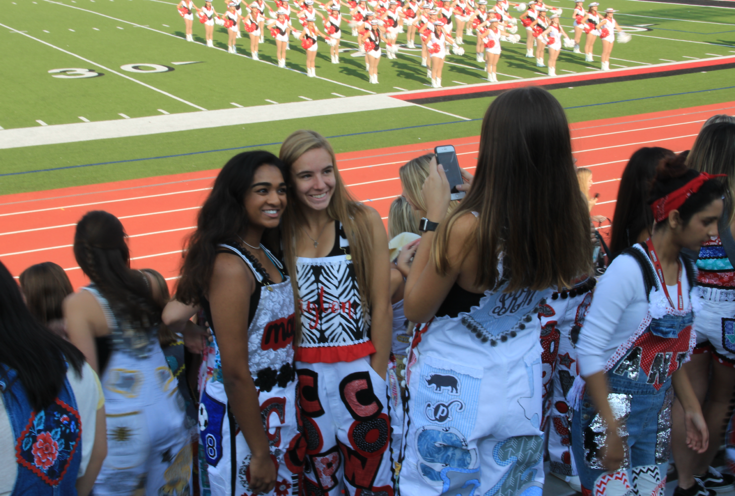 Coppell High School seniors Maya Joseph and Payton Kirk pose on Sept. 8 during the first pep rally of the year wearing their senior overalls. Senior overalls are worn during the school day before Friday night home football games and have been a tradition among schools in Texas.