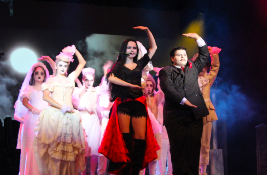 """Coppell High School seniors Macy Johnson, who plays  Morticia Addams, and Mark Beshai who plays Gomez Addams, sing during a romantic scene of """"The Addams Family"""" on Saturday night in the auditorium. """"The Addams Family"""" musical will also be performed this Friday, Saturday and Sunday."""