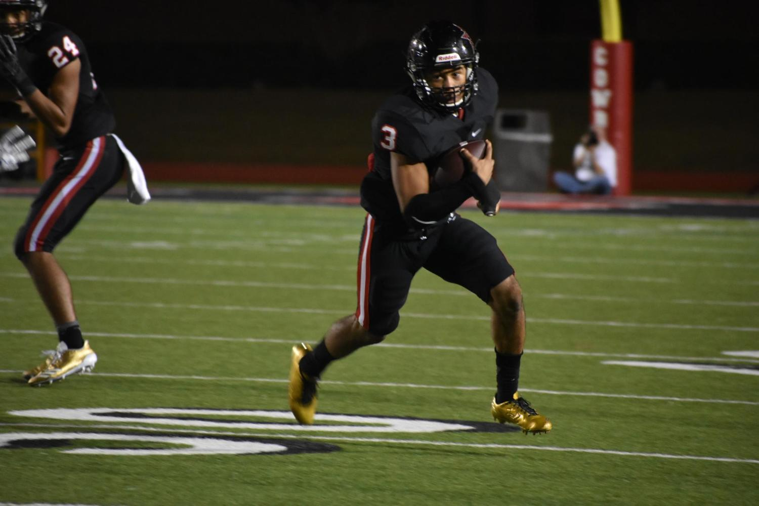 Coppell junior safety Jonathan McGill carries the ball during the first quarter of Friday night's game at Buddy Echols Field. McGill had two touchdowns for the Cowboys as they defeated the Jesuit Rangers, 63- 41.