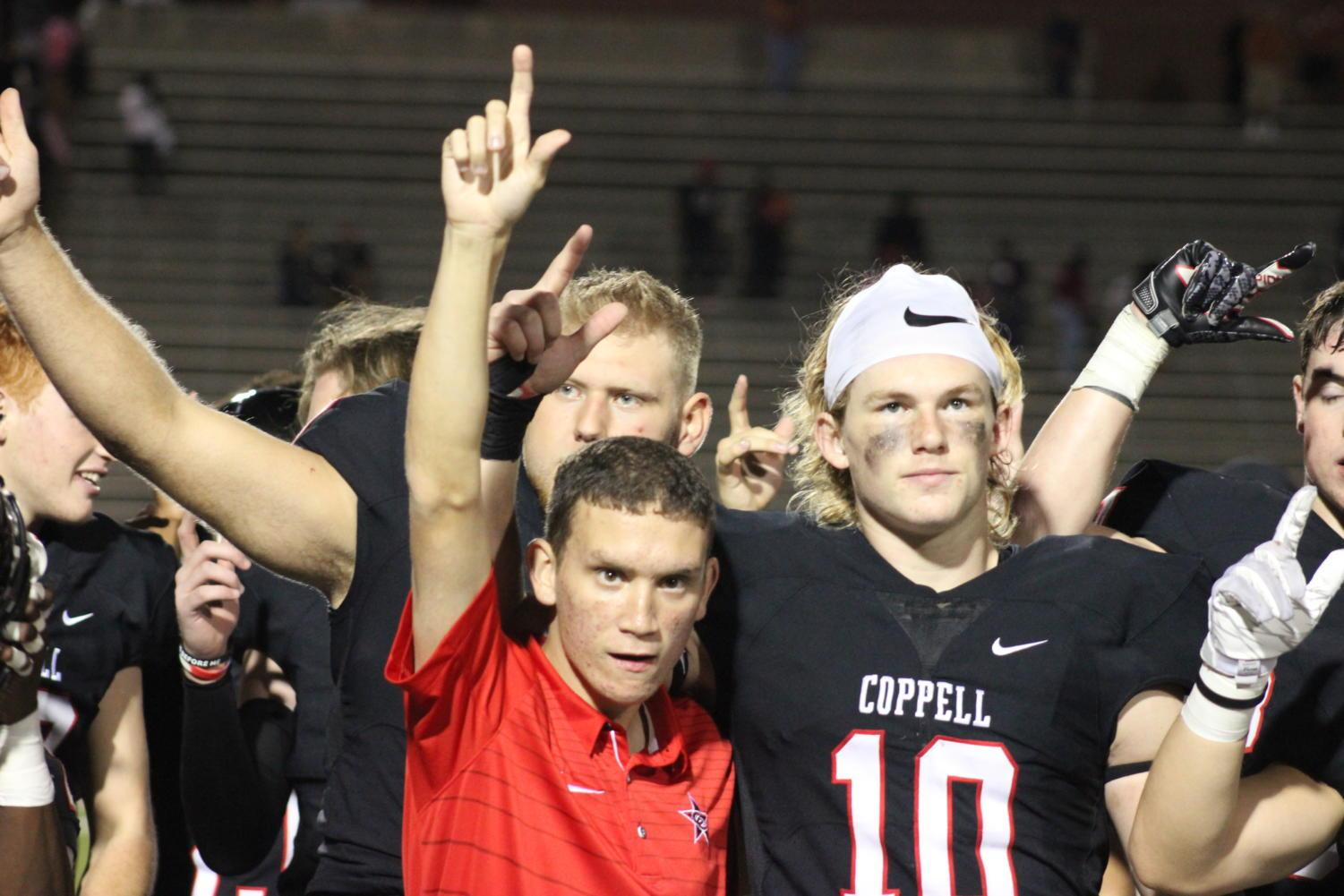 The Coppell Cowboys football team lines up for the school alma mater following its 55-14 victory over W.T. White on Friday at Buddy Echols Field. Coppel junior outside linebacker Jay Dempsey stands with assistant football coach Cole Bryant.