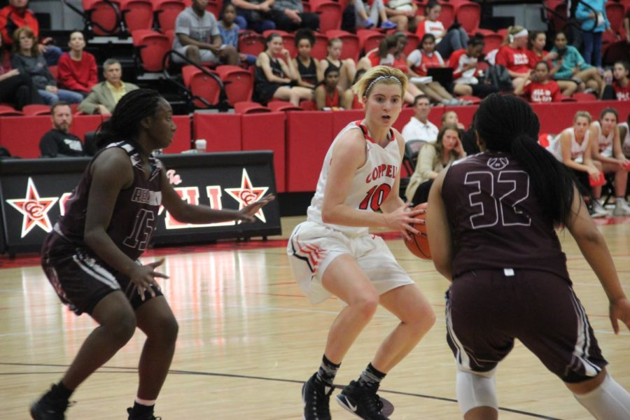 Coppell High School senior Mary Luckett dribbles the ball down the court during Tuesday night's game at CHS arena. The Cowgirls take a loss the first game of the season against Red Oak 47-54.      Photo by Bren Flechtner