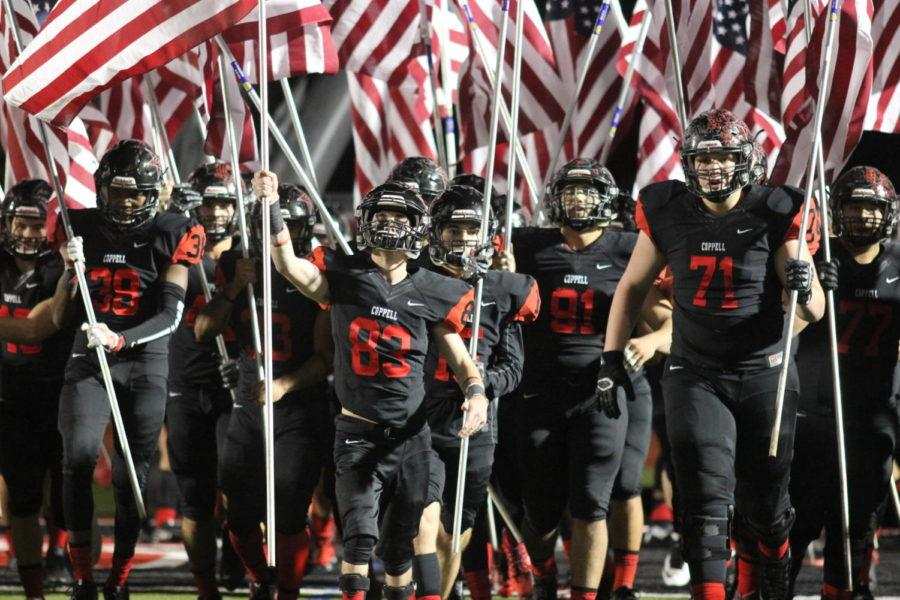 The Coppell Cowboys march out with American Flags before the game on Nov. 10 at Buddy Echols Field. The Cowboys commemorate the men and women that dedicate their lives to the United States for Veterans Day.