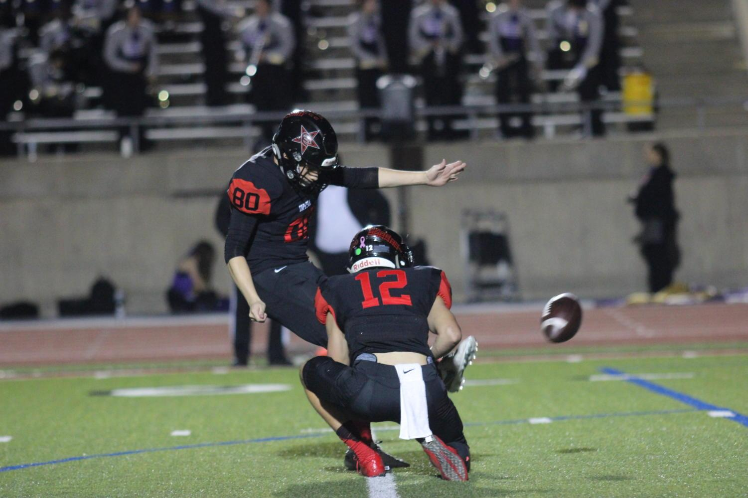 Coppell+Cowboys+senior+kicker+Sebastian+Escalante+kicks+as+senior+wide+receiver+Michael+Quirk+stabilizes+the+ball+during+the+fourth+quarter+on+Nov.+10+at+Buddy+Echols+Field.+The+Coppell+Cowboys+defeated+the+Richardson+Eagles%2C+49-14.+