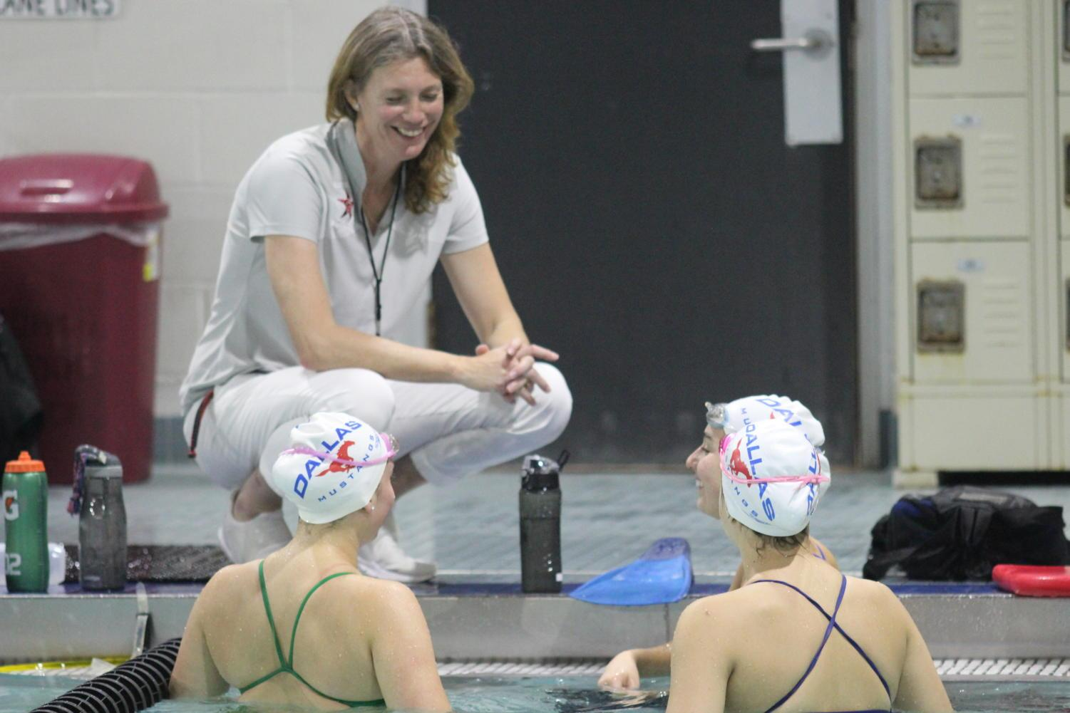 Coppell seniors Gabi Badillo, Anna Wilcox and Sophie Wilcox discuss their practice laps with Coppell swimming coach  Marieke Roberts during swim practice on Oct. 19 at the Coppell YMCA. Roberts encourages the swimmers to continue working hard to improve their speed and persistence in the pool.