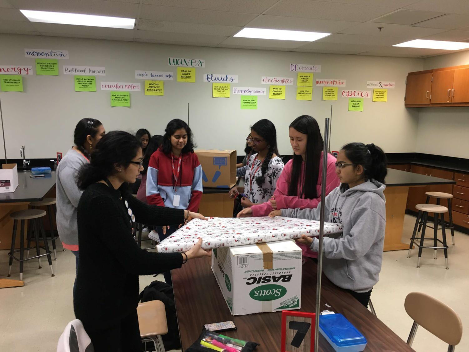 Coppell High School sophomores Shriya Vanparia, Dania Nesar, Trisha Narwekar, Harsha Alexander, Eva Theel and Rifhat Sindhi wrap donation boxes for their Habitat for Humanity supply drive at their first club meeting on Thursday, Nov. 9. They will be collecting home supplies until Dec. 15.