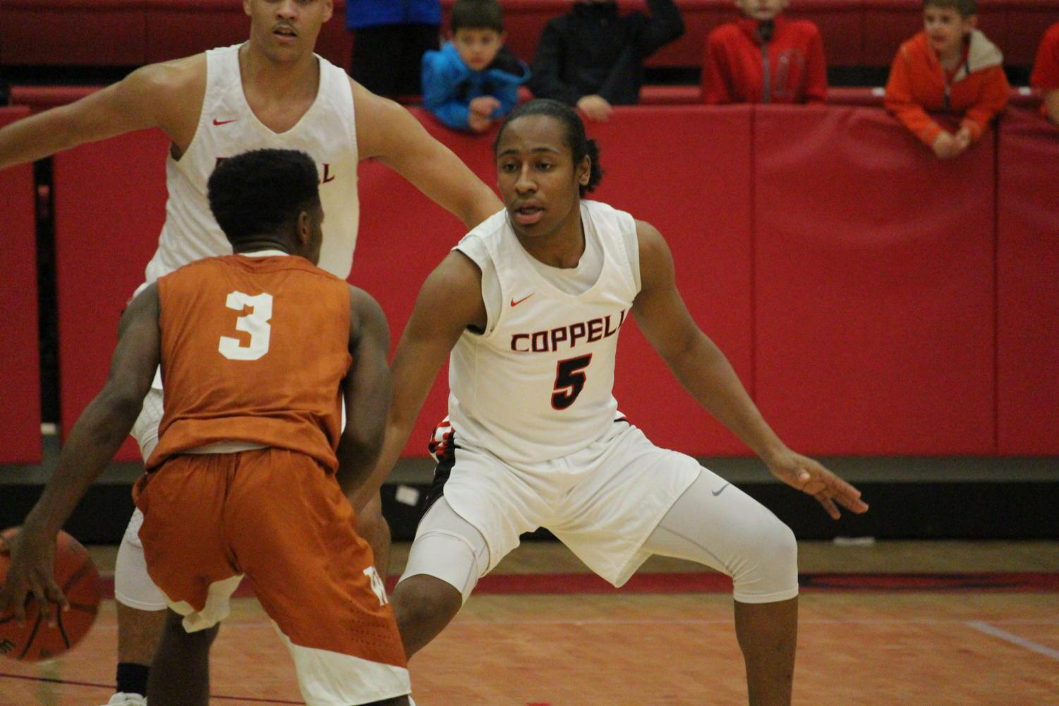 Coppell+High+School+senior+Jaylon+Wilson+plays+defense+during+the+second+quarter+of+Friday+nights+game+in+the+arena.+The+varsity+boys+basketball+team+played+a+home+game+against+WT+White+high+school+taking+the+win+with+a+score+of+74-52.