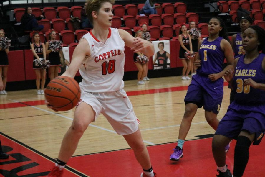 Coppell High School sophomore Mary Luckett runs and makes a pass. The girls varsity basketball team played against Richardson Friday night, Richardson took the win by five points, the final score being 52-57.