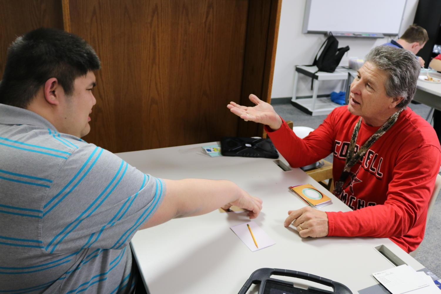 Coppell High School student Nathaniel Umlas  learns Intensive Teacher training (ITT) cards with special needs teacher, Ed Beal, in the new education room D101. Beal moved his special needs classroom from C hall to D hall this school year for a more spacious and accessible learning room for students.