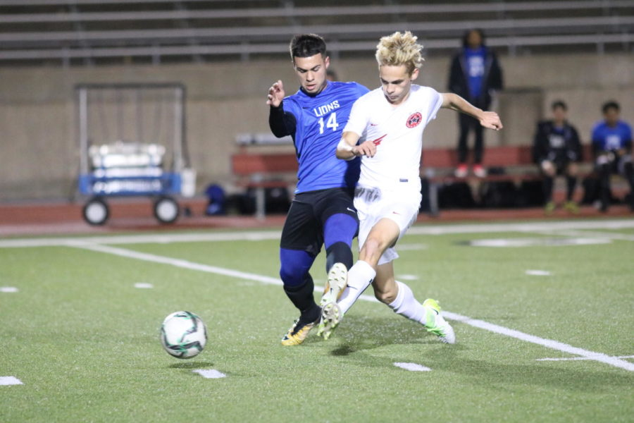 Coppell Cowboys senior defender Josh Strong makes a pass as John Tyler Lions junior Frankie Sanchez tries to block it during the first half of the game on Jan. 23 at Buddy Echols Field. The Coppell Cowboys defeated the John Tyler Lions 2-0.