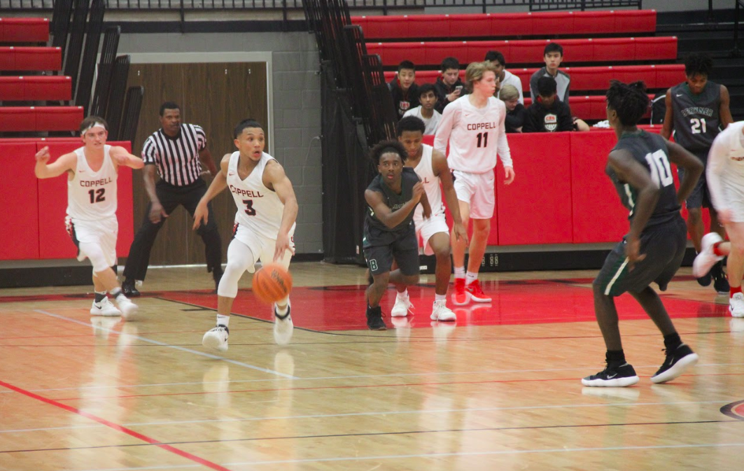 Coppell High School junior Tariq Aman recovers the ball from defense and dribbles it down court during Friday nights game in the arena. The Cowboys won with a score of 81-59 against the Berkner Rams.