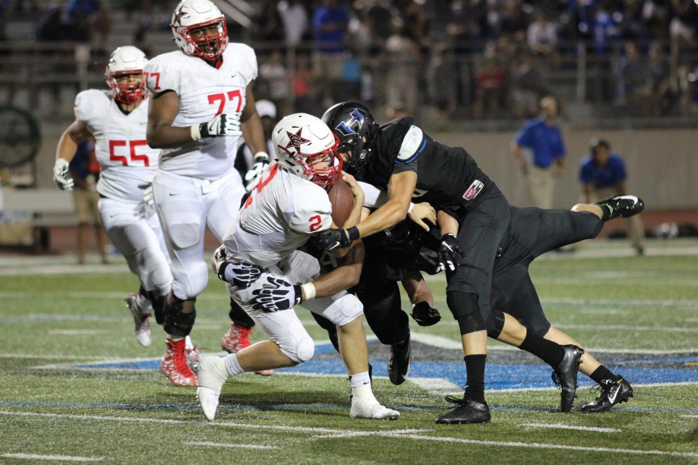 Coppell High School sophomore quarterback Brady McBride runs through the Hebron defense. Coppell won the game 26-20. Photo by Amanda Hair.